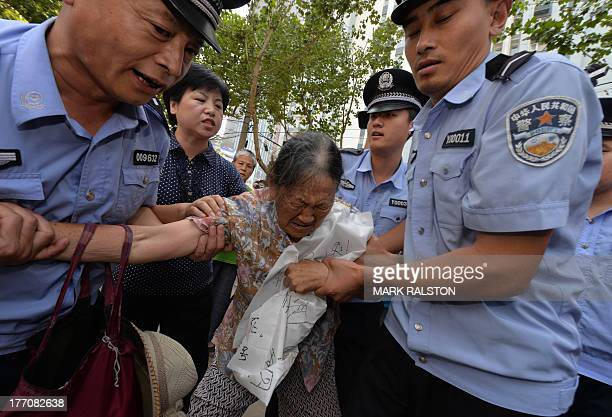 Police detain an elderly demonstrator who was protesting against the Chinese justice system on August 21 2013 outside the Intermediate People's Court...
