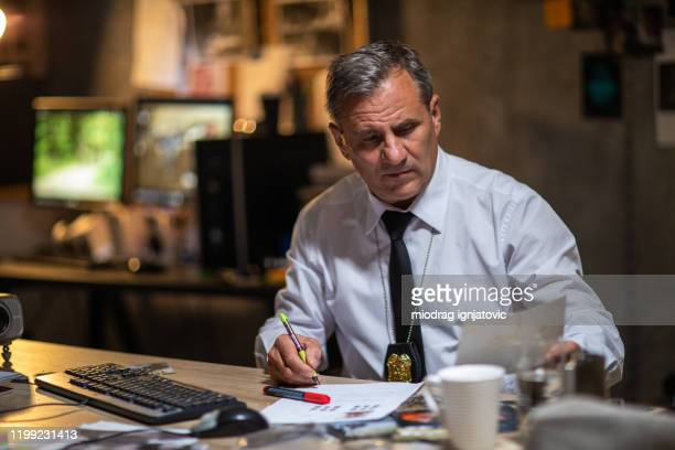 police detective finishing work late at night - police chief stock pictures, royalty-free photos & images