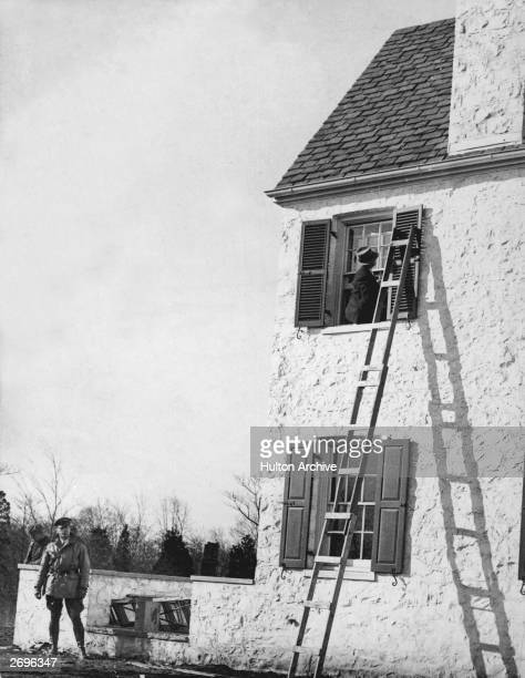 Police detective leans out the nursery window of American aviator Charles Lindbergh's home to examine the ladder which was used in the kidnapping of...