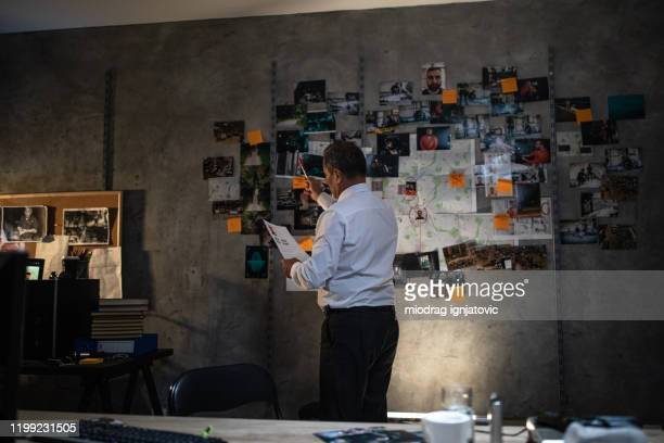 police detective looking at the paper in front of the wall with map and pictures at office - police station stock pictures, royalty-free photos & images