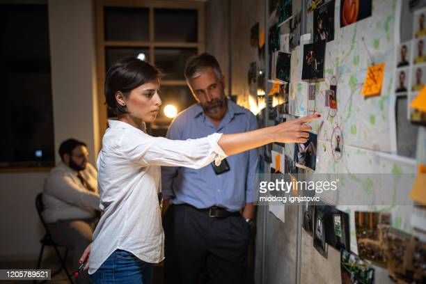 police detective showing criminal's location to colleague on map attached to a wall - privateinvestigator stock pictures, royalty-free photos & images