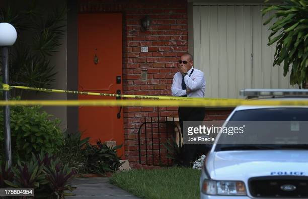 A police detective stands near the orange door which is the front door to a townhouse where seemingly a husband reportedly confessed on Facebook to...