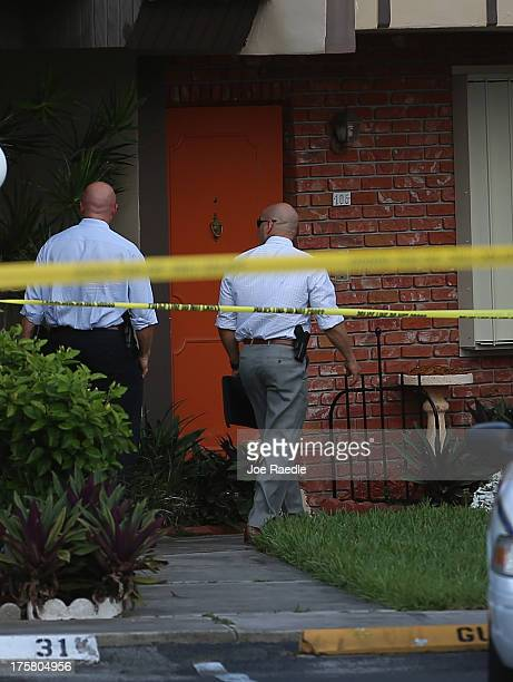 Police detectives walk past the orange door which is the front door to a townhouse where seemingly a husband reportedly confessed on Facebook to...