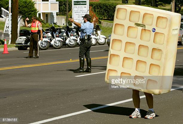 Police direct traffic as a antiKerry protester dressed in a waffle suit stands outside a town hall meeting where Democratic presidential candidate...