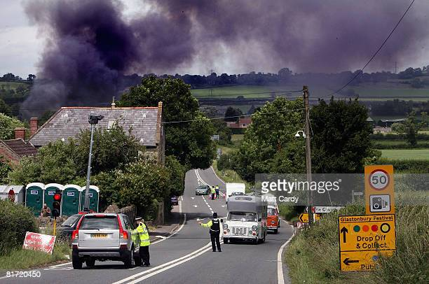 Police direct traffic away from a scrap car yard fire that has caused dispruption to people arriving at the site at the Glastonbury Festival at...