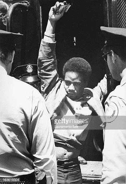 Police disarm Emory Douglas a member of the Black Panthers after the group's protest at the California Assembly in May 1967 in Sacramento California
