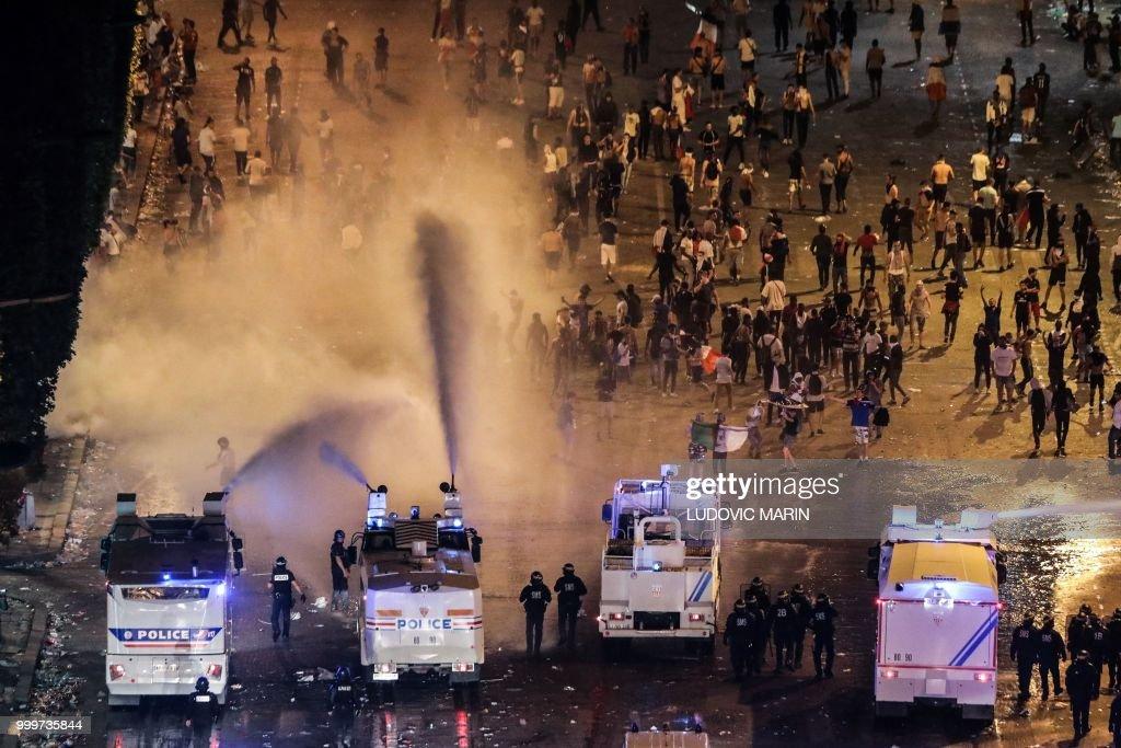 TOPSHOT - Police dispers people with water canons after celebrations following the Russia 2018 World Cup final football match between France and Croatia, on the Champs-Elysees avenue in Paris on July 15, 2018. - France won 4-2.