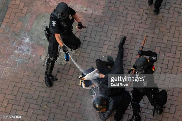 Police disperse demonstrators with pepper spray during protests in Seattle on July 25, 2020 in Seattle, Washington. Police and demonstrators clash as...