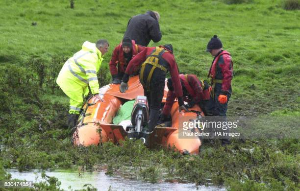 Police divers and paramedics recover a body during the search for two girls who were swept away while 'river walking' in a swollen beck during a...