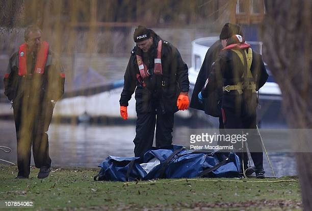 Police divers examine a bag containing a body removed from The River Thames on January 3 2011 in Shepperton England Six people were on a small boat...