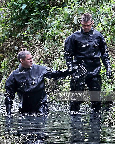 Police divers hold up an item as they search the river Brent for clues in the hunt for missing school girl Alice Gross on September 25 2014 in London...