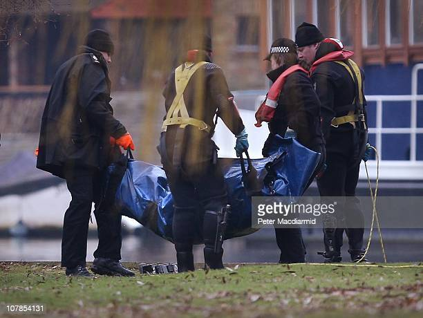 Police divers remove a bag containing a body recovered from The River Thames on January 3 2011 in Shepperton England Six people were on a small boat...