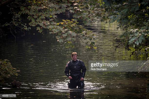 Police divers walk through the River Brent in the area where police are searching for missing schoolgirl Alice Gross on September 23 2014 in London...