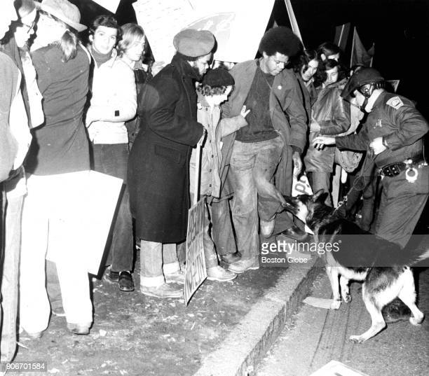 A police dog bites the pant leg of a demonstrator during a protest against an appearance by First Lady Pat Nixon for a Republican gala at the...