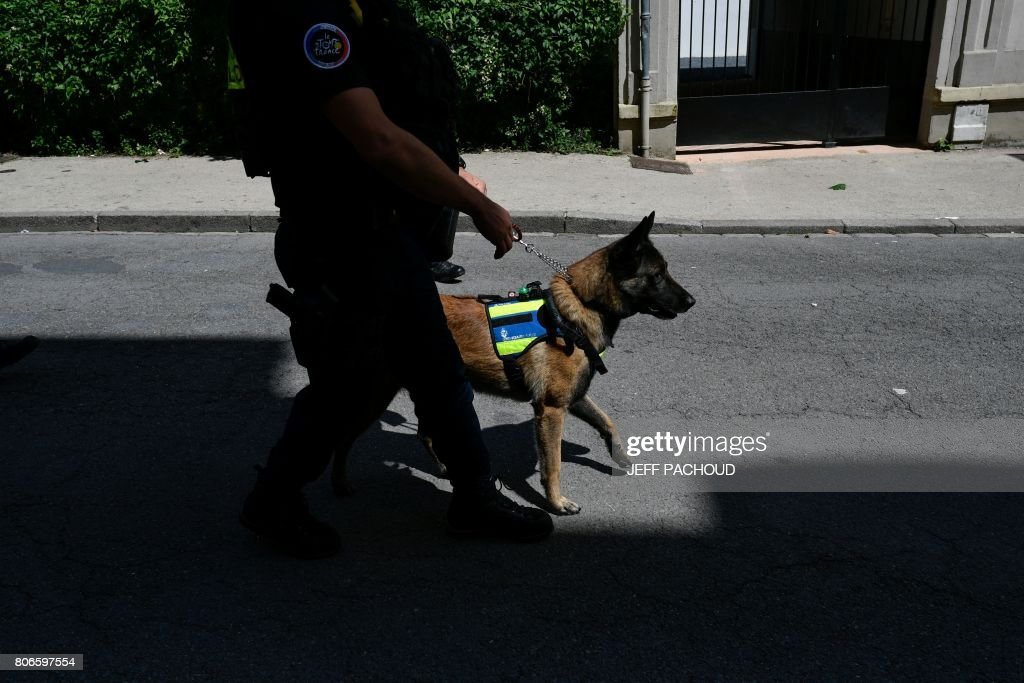 TOPSHOT - Police dog handler patrols with his sniffer dog near the finish line as part of the 212,5 km third stage of the 104th edition of the Tour de France cycling race on July 3, 2017 between Verviers, Belgium and Longwy, France. / AFP PHOTO / Jeff PACHOUD