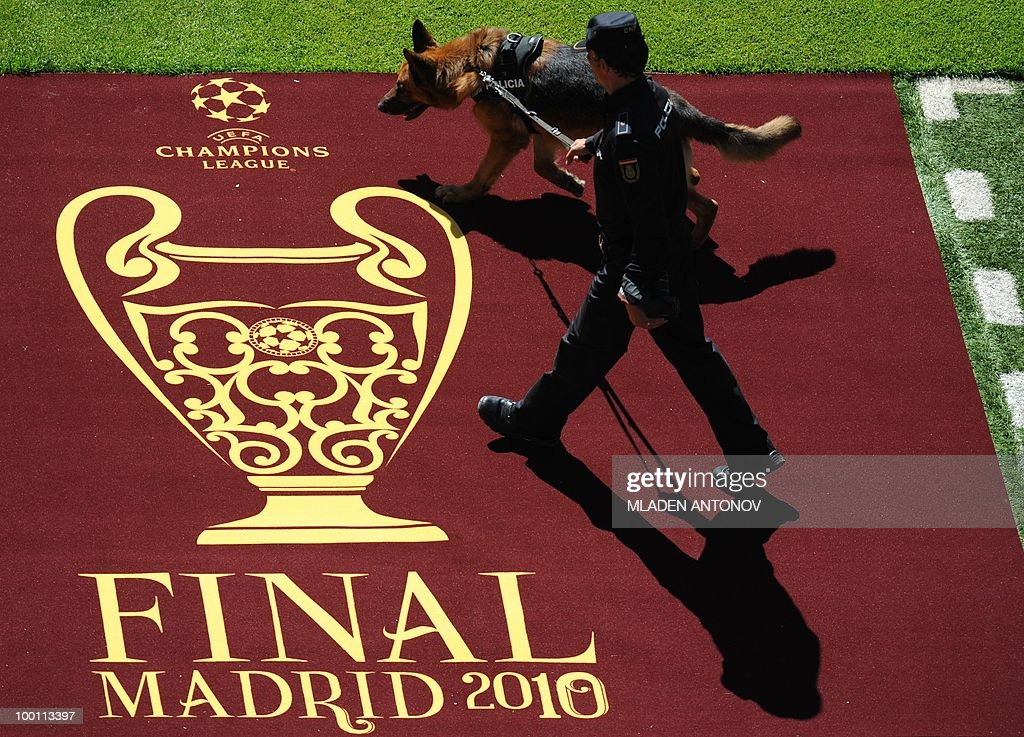 A police dog handler walks by the entrance to the pitch at the Santiago Bernabeu stadium in Madrid on May 21, 2010 on the eve of the UEFA Champions League final football match. Inter Milan will face Bayern Munich in the UEFA Champions League final match to be played at the Santiago Bernabeu Stadium in Madrid on May 22, 2010.