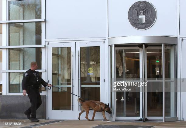 Police dog sniffs around the front entrance of the United States District Court Greenbelt Division on February 21 2019 in Greenbelt Maryland A member...