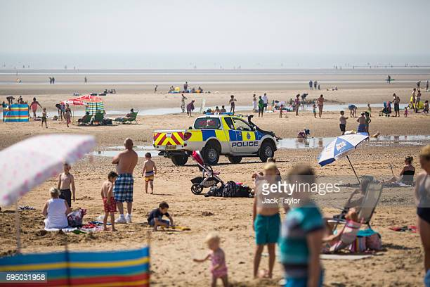 Police drive along Camber Sands on August 25 2016 in Rye England Five men were found dead after being pulled from the sea on the hottest day of the...