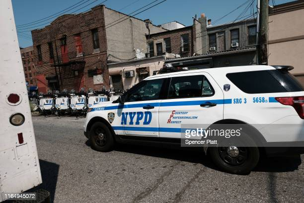 Police drive down a block in the Brownsville neighborhood in Brooklyn near where one person was shot and killed and 11 others were injured after two...
