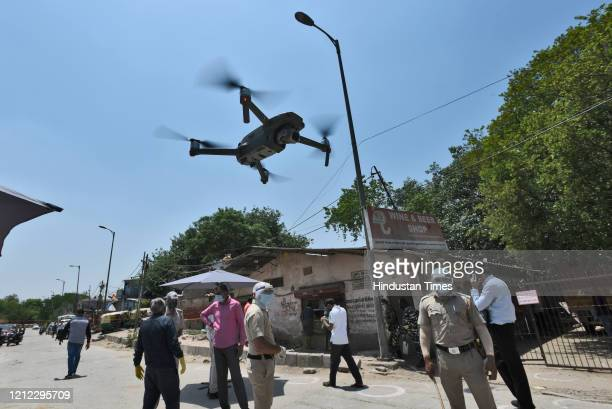 Police drone camera keeping vigil as people wait for their turn to buy alcohol from a liquor shop after Delhi government issued e-tokens, specifying...