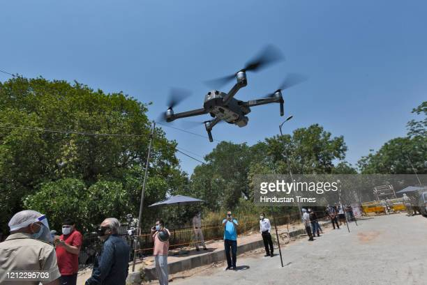 Police drone is launched as people wait for their turn in a long queue to buy alcohol outside a liquor shop after Delhi government issued e-tokens,...