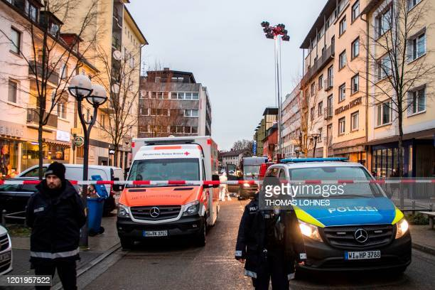 Police emergency services and forensic police are seen behind a police cordon near a bar in the centre of Hanau near Frankfurt am Main western...