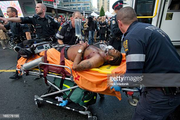 120602 TORONTO ONTARIO Police EMS and Firefighters wheel an adult male with what appears to be more than one gunshot to his upper left chest towards...