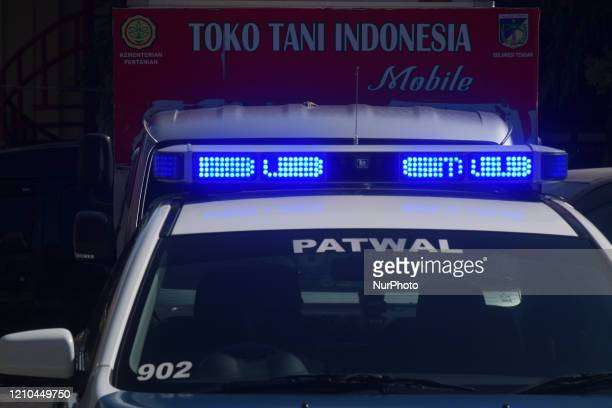 Police escort a car carrying food at a mobile market held by the local government in Palu, Central Sulawesi Province, Indonesia, on April 20, 2020....