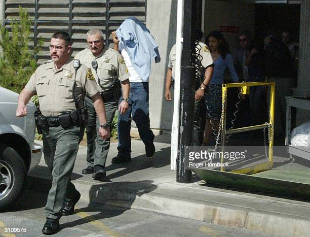 Police escort a group of people believed to be family members of Marcus Wesson from the courthouse on March 18 2004 in Fresno California Wesson's...