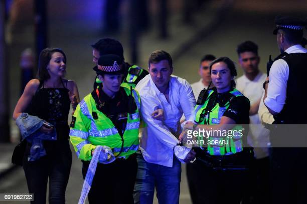 Police escort a member of public as they clear the scene of a terror attack on London Bridge in central London on June 3 2017 Armed police opened...