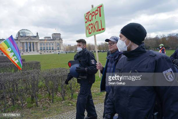 Police escort a protester holding a sign critical of German Chancellor Angela Merkel outside the Reichstag on April 13, 2021 in Berlin, Germany....