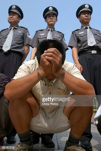 Police escort a suspect accused of disturbance of public order during a public sentence at a railway station on June 28 2005 in Beijing China The...
