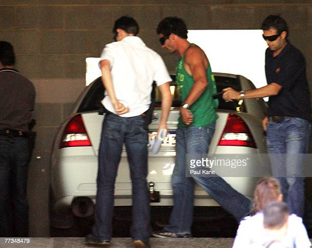Police escort AFL player Ben Cousins into Curtin House for questioning after being arrested in Perth October 16 2007 in Perth Australia