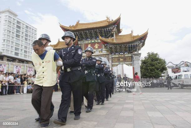 Police escort criminals being convicted of abducting and selling children during a public sentence on June 12, 2005 in Kunming of Yunnan Province,...