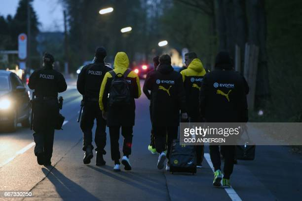 TOPSHOT Police escort Dortmund's players after the team bus of Borussia Dortmund had some windows broken by an explosion some 10km away from the...