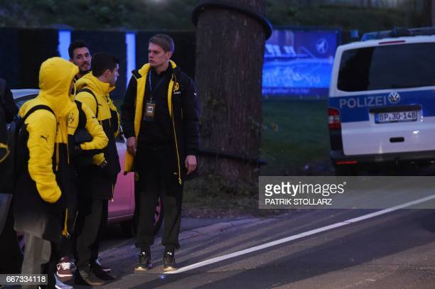 Police escort Dortmund's players after the team bus of Borussia Dortmund had some windows broken by an explosion some 10km away from the stadium...