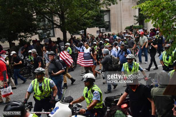 Police escort farright demonstrators during a rally at Lafayette Park opposite the White House August 12 2018 in Washington DC one year after the...