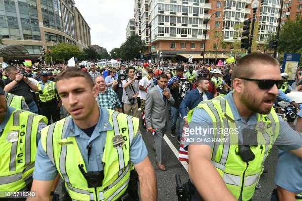 Police escort far-right demonstrators during a rally at Lafayette Park opposite the White House August 12, 2018 in Washington, DC, one year after the...