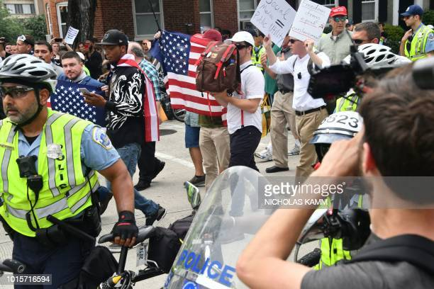 Police escort farright demonstrators some hidding their faces during a rally at Lafayette Park opposite the White House August 12 2018 in Washington...