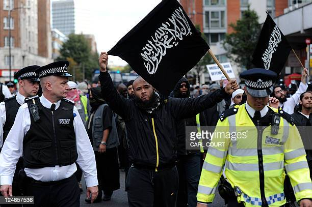 Police escort Islamist demonstrator marching to protest outside the US embassy in London on September 11 2011 before a ceremony to mark the 10th...