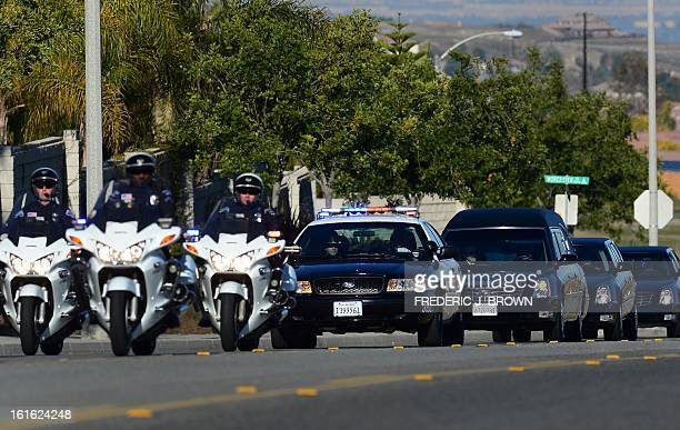 Police escort leads a convoy of vehicles including the hearse carrying the body of slain Riverside police officer Michael Crain on its approach to...