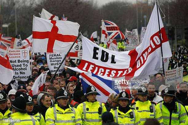 Police escort members of the English Defence League as they march holding banners aloft during a demonstration through the streets of Leicester on...
