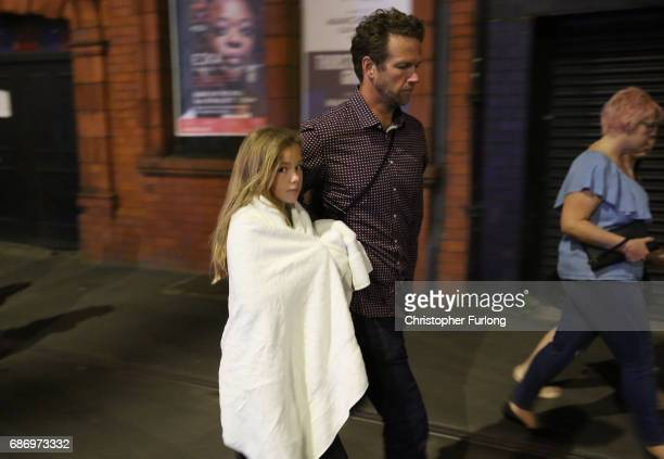 Police escort members of the public from the Manchester Arena on May 23, 2017 in Manchester, England. An explosion occurred at Manchester Arena as...