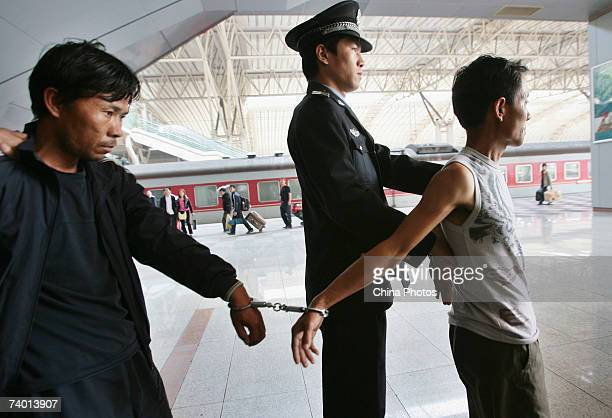 Police escort men suspected of being involved in the abduction and sale of women at the Nanjing Railway Station on April 27 2007 in Nanjing of...