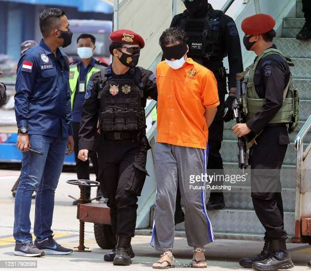 Police escort one of the group of 22 terror suspects of the Al-Qaeda-linked Jemaah Islamiyah that are being transferred to Jakarta from East Java, at...