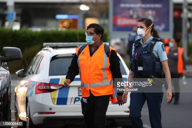 Police escort people from LynnMall to their cars after a violent extremist took out a terrorist attack stabbing six people before being shot by...