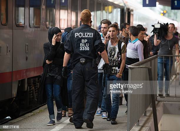 Police escort refugees at a train station on September 14 2015 in Freilassing Germany Germany has temporarily introduced controls along its border...