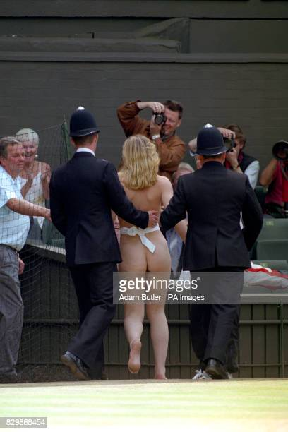 Police escort streaker Melissa Johnson off of Centre Court this afternoon at the start of the Mens' Singles Final