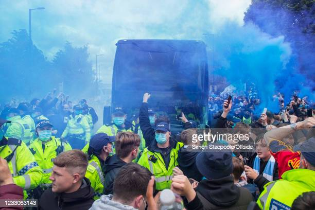 Police escort the Manchester City team coach as fans let off blue flares before the Premier League match between Manchester City and Everton at...