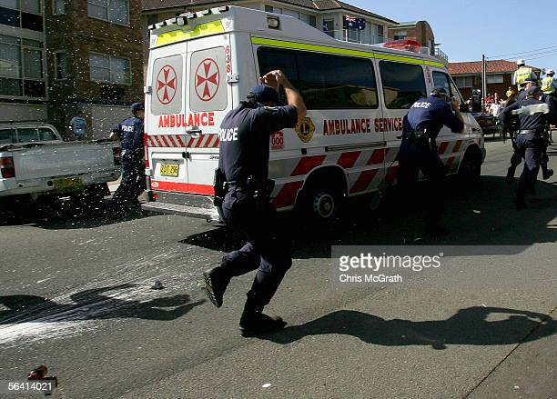 Police escorting an Ambulance are pelted with beer bottles on Cronulla Beach December 11 2005 in Sydney Australia Despite a massive police presence...